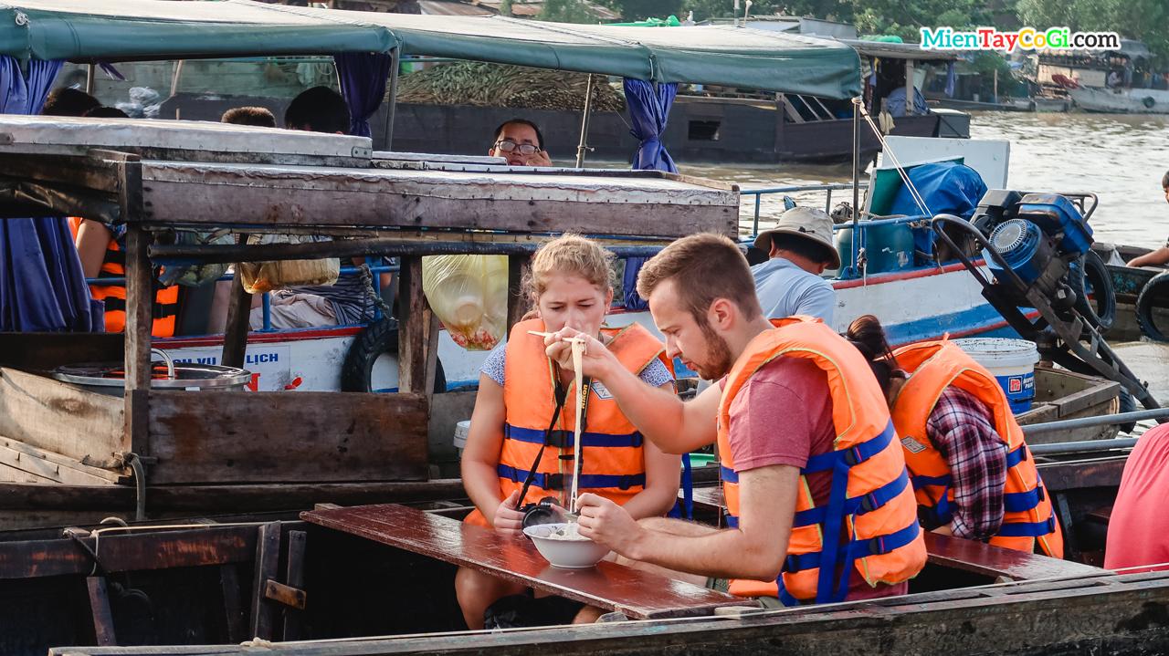 Khách du lịch nước ngoài trải nghiệm ăn hủ tiếu trên ghe