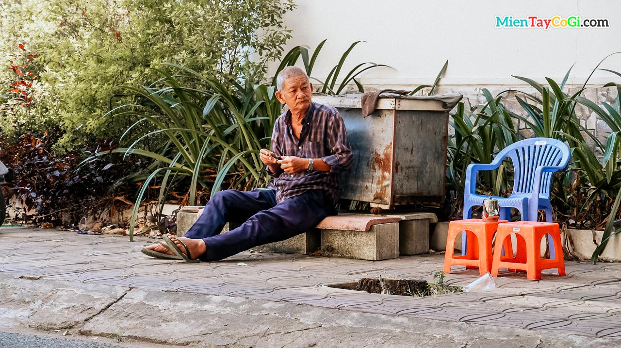 Một ông cụ ngồi ven đường