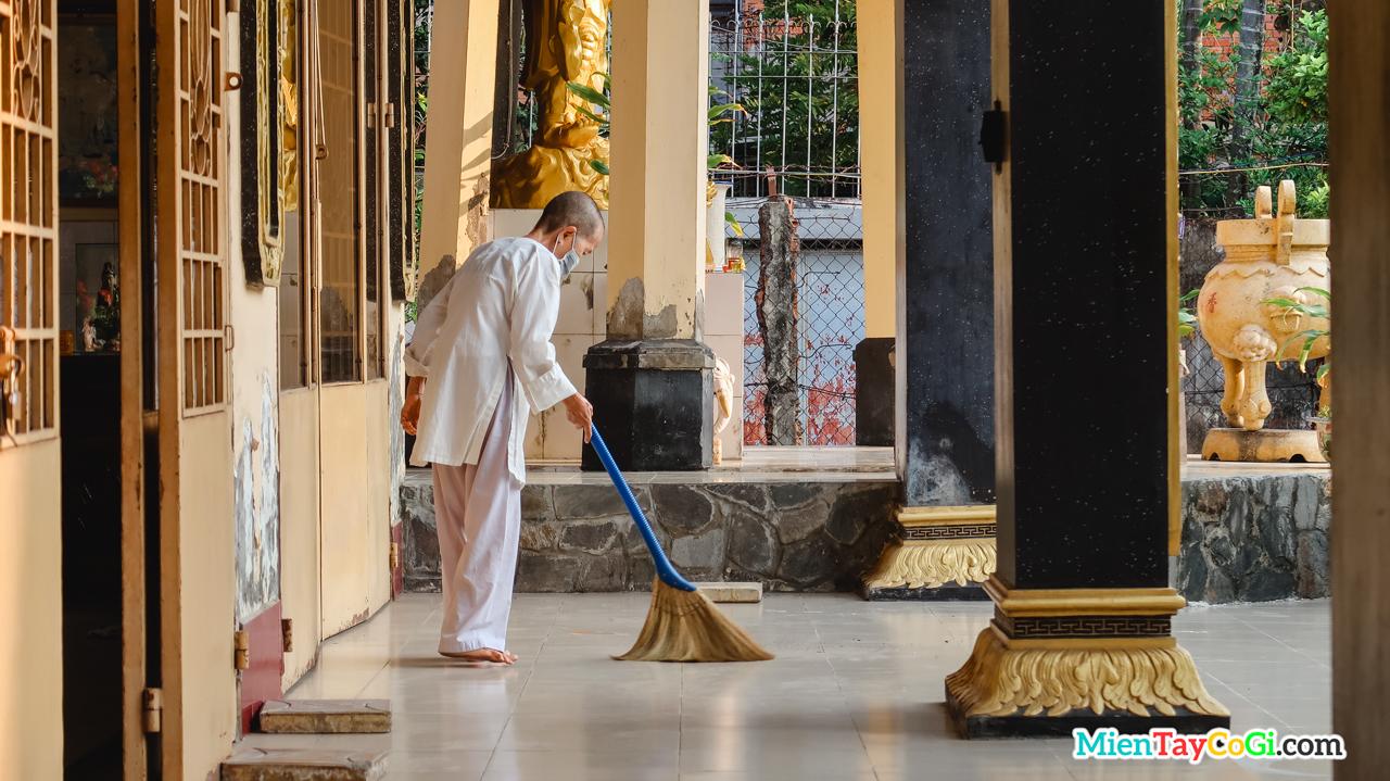 Một sư cô đang quét dọn vệ sinh chùa