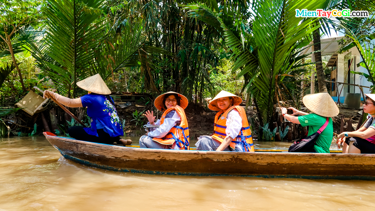 Tourists sit on a three-leaf boat to explore Con Thoi Son