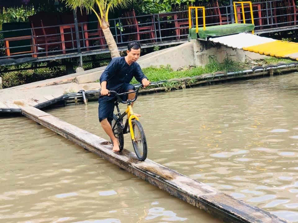 Đạp xe qua cầu ván tại khu du lịch Ông Đề Cần Thơ