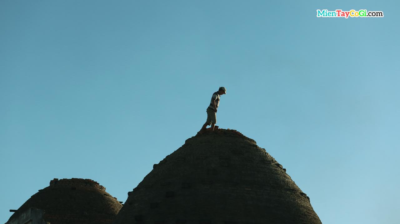 Một người dân leo lên nóc lò gạch để xem xét