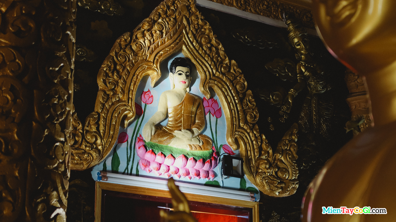 Nhiều tượng Phật nhỏ được điêu khắc trên tường ở chánh điện