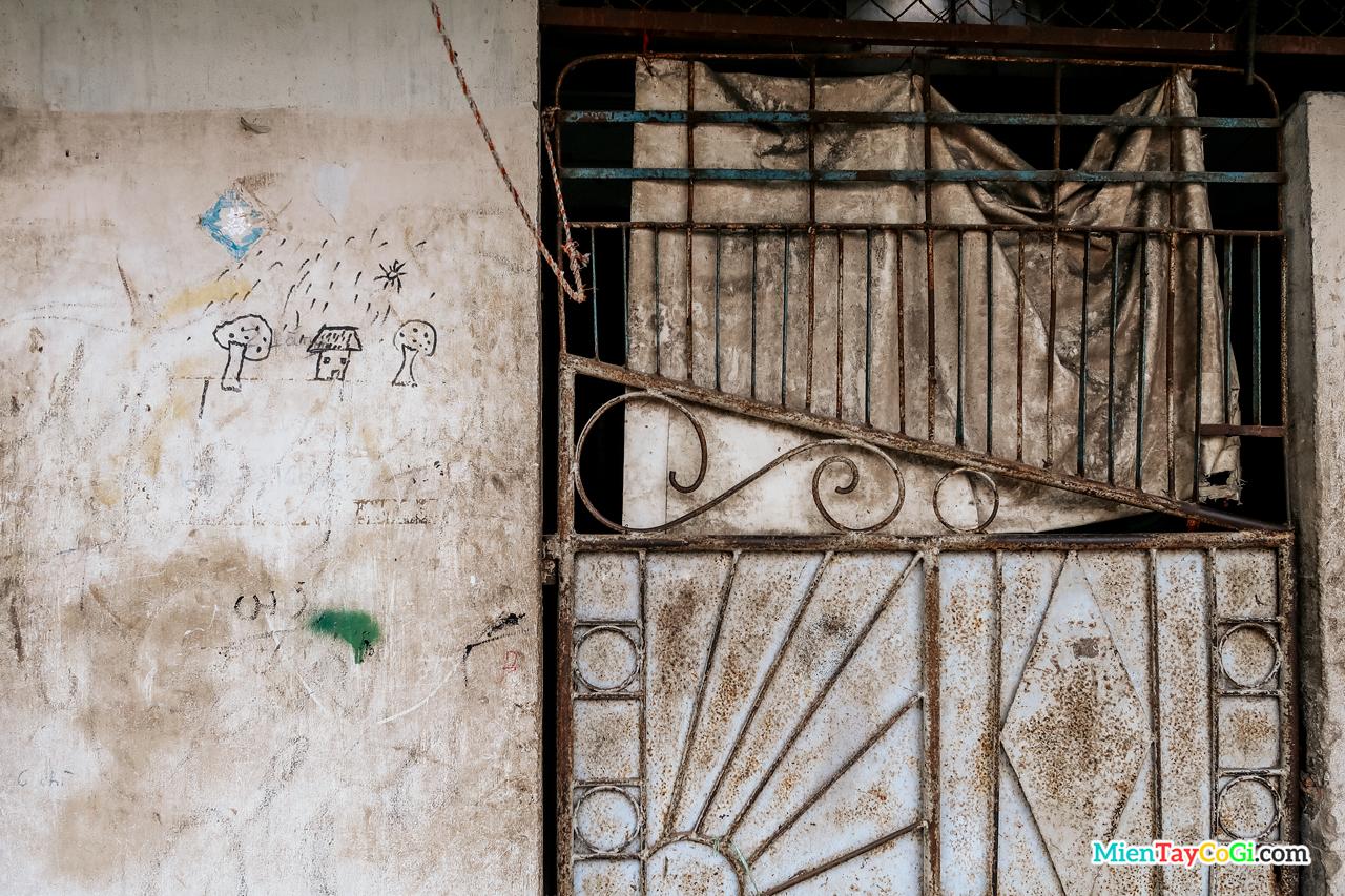 Bức tường lem luốt bên cạnh một cổng vào trong 1 khu nhà tại trung tâm thành phố Cần Thơ
