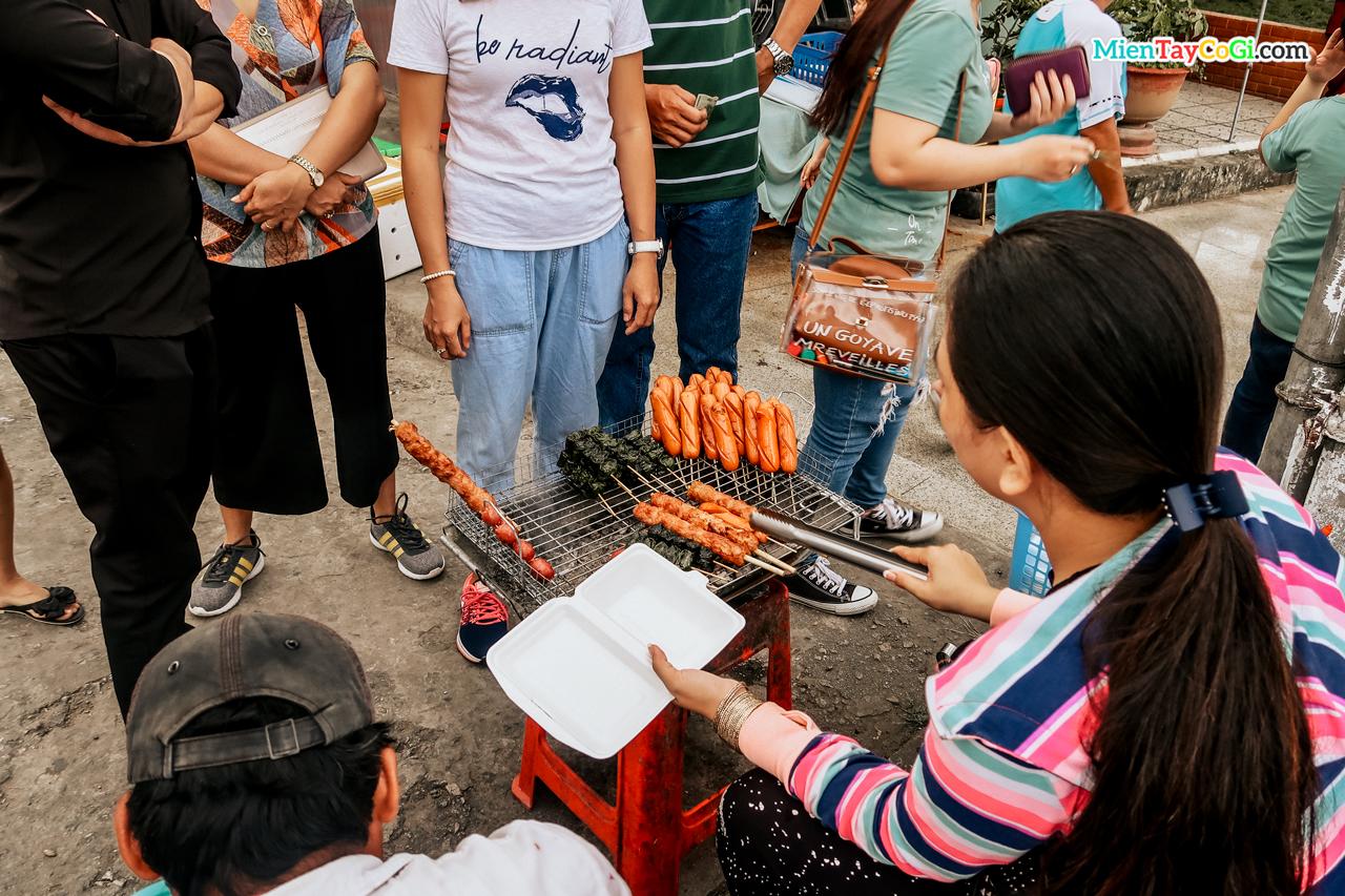 Mọi người quây xung quanh hàng đồ nướng ở bến Ninh Kiều trước khi đi chợ nổi Cái Răng