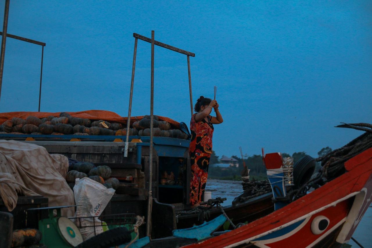 Một người dân đang cúng tàu tại chợ nổi Long Xuyên