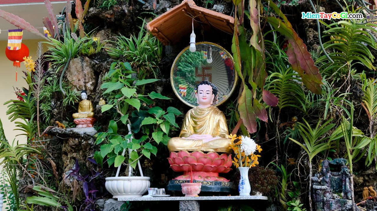 Tượng Phật Đà nhỏ đặt giữa hòn non bộ trước chánh điện chùa Hiệp Minh
