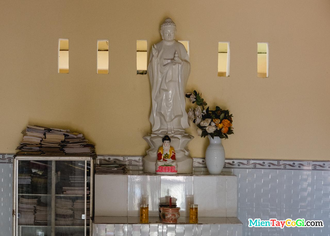 Tượng Phật A Di Đà gần kệ sách trong chùa