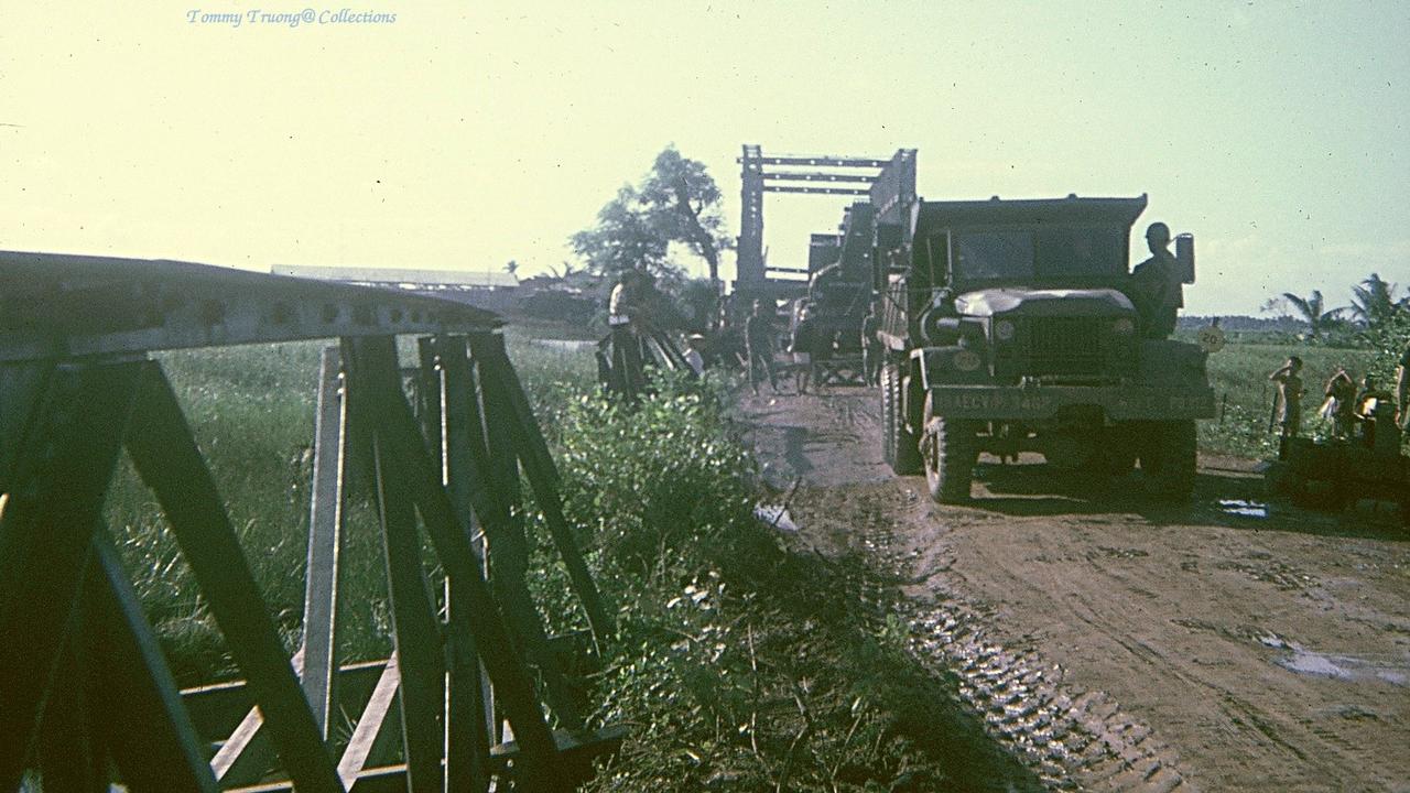 Xe tải chở vật liệu xây dựng lại cây cầu huyết mạch bị đánh bom ở Bến Lức năm 1966 - 1967 | Photo by Tom Jackson