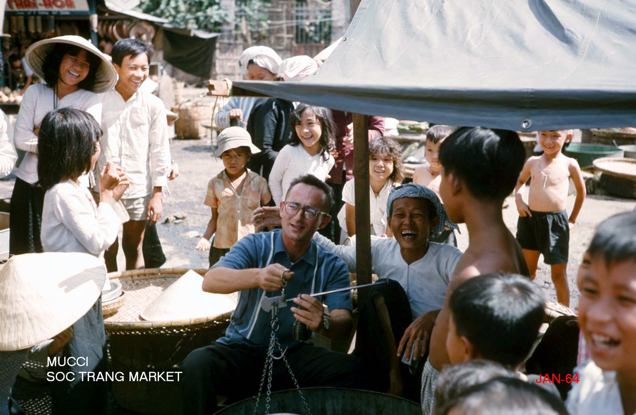 Tác giả Mucci vui vẻ cùng lũ trẻ và người bán hàng bên cây cân xưa ở chợ Sóc Trăng năm 1964 - Photo by George Muccianti