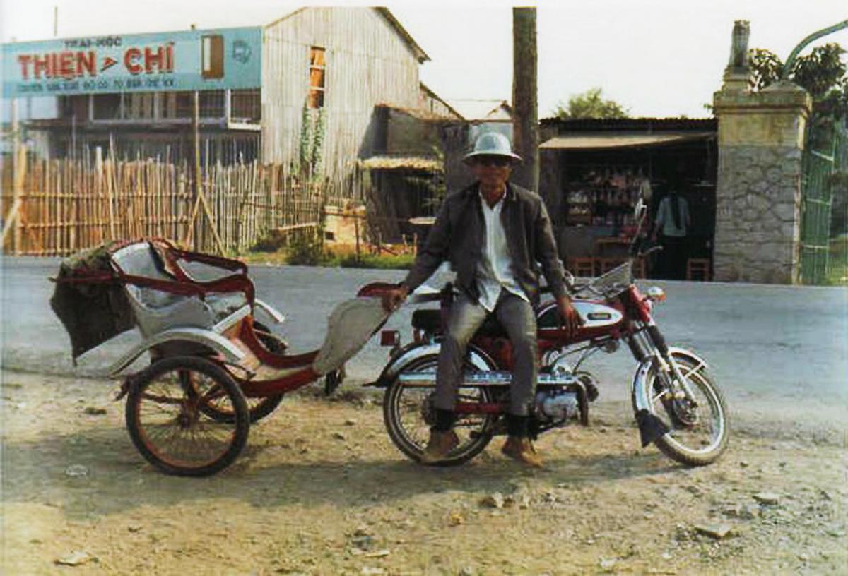 Người lái xe ba gác chụp hình trước trại mộc Thiện Chí năm 1965 - 1971 | Photo by William Jones