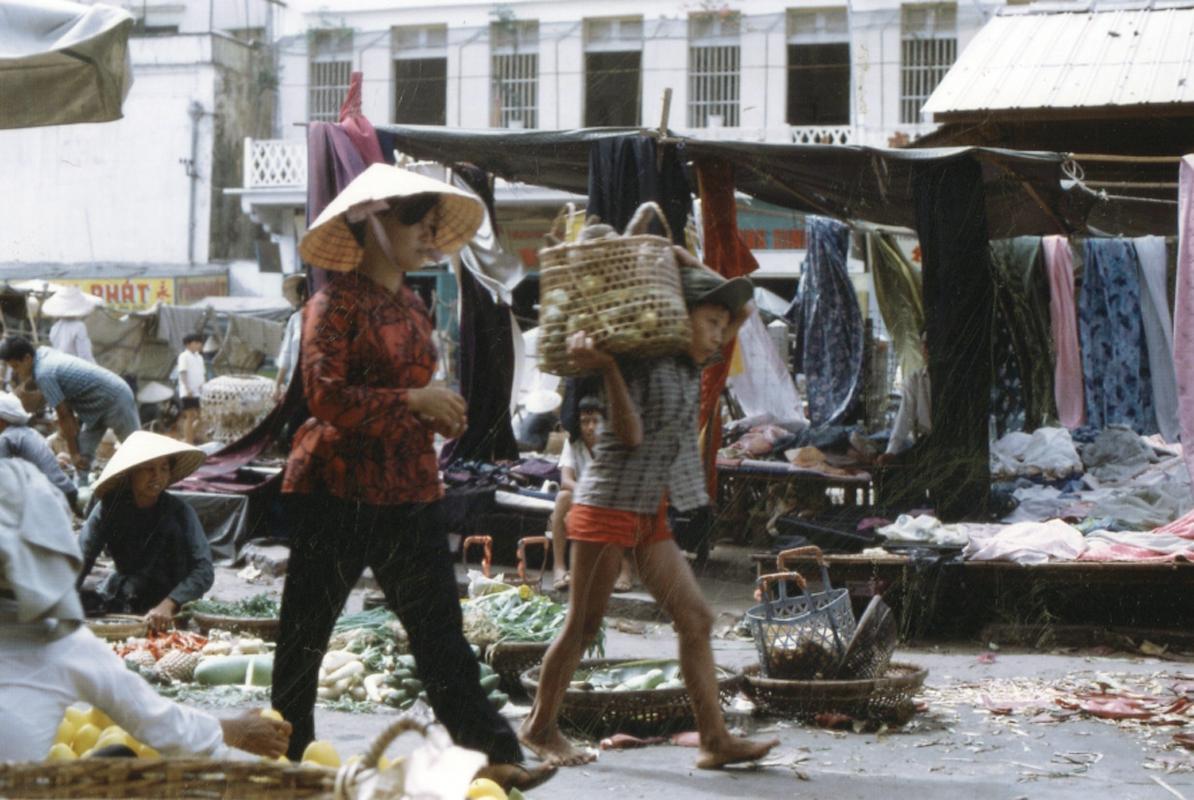 Đứa nhỏ gành hàng trên vay đi qua chợ Cần Thơ xưa