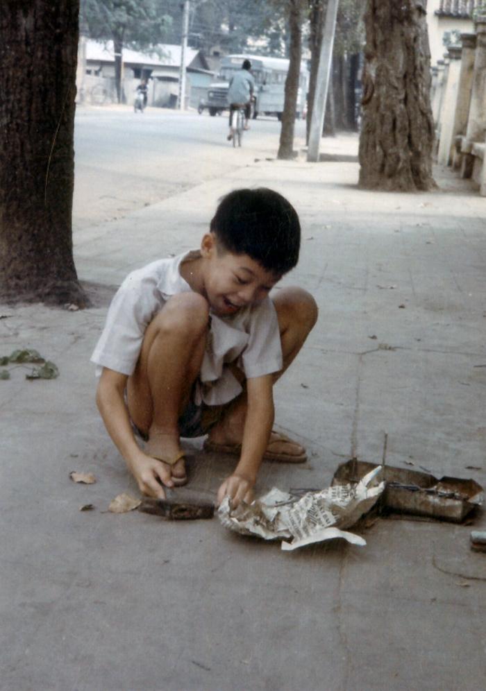 Đứa trẻ nhỏ với búa và đinh trên 1 con phố