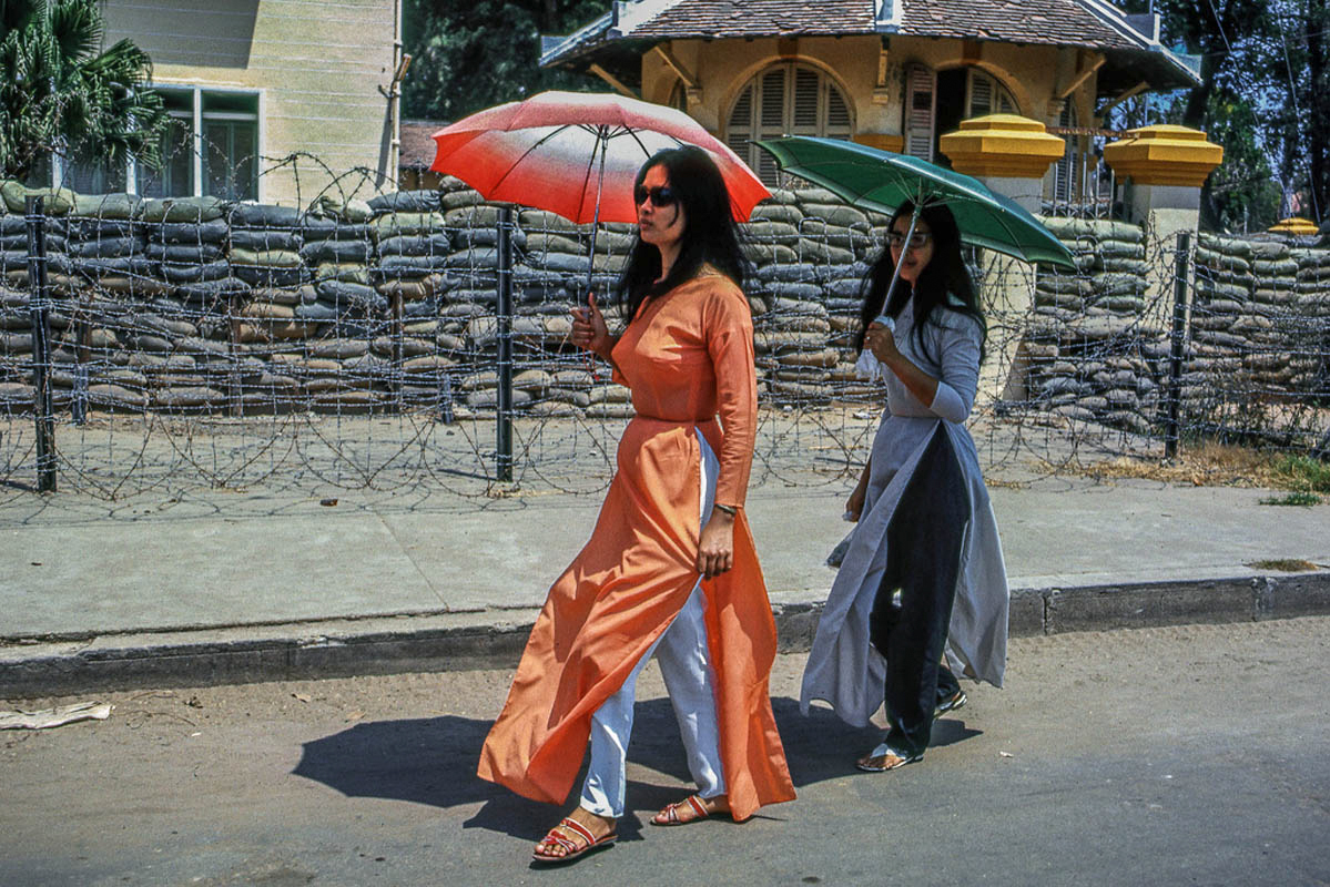 Hai phụ nữ trong trang phục áo dài đi ngang qua hàng rào kẽm gai và bao cát
