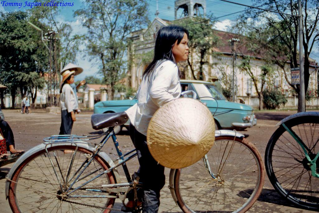 Một người phụ nữ chạy xe đạp trước nhà thờ Mỹ Tho
