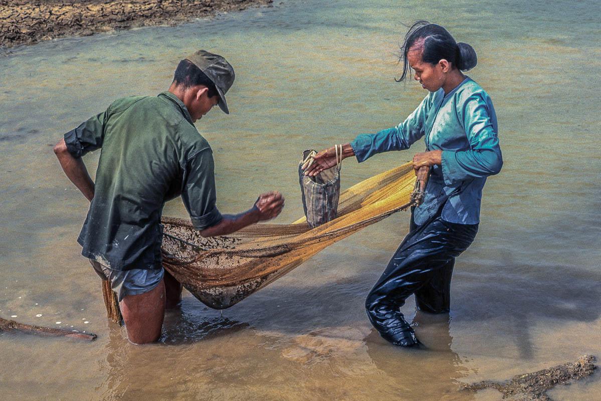 Người lính VNCH và vợ vét lưới những con cá cuối cùng trong ao nước mưa đang khô cạn cạnh sân bay Bình Đức phía Tây Mỹ Tho năm 1969