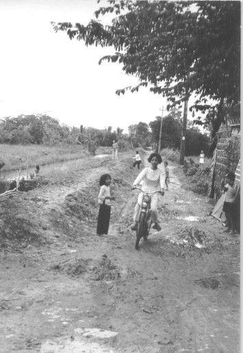 Người phụ nữ trẻ mặc áo dài chạy xe máy qua 1 con đường sinh lầy ở Cần Thơ năm 1965