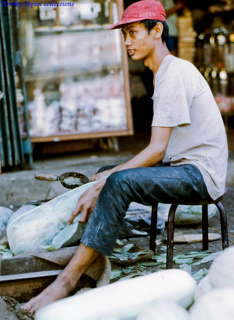 Chàng trai gọt bí làm mứt ngày Tết ở chợ Mỹ Tho năm 1969   Photo by Lance Cromwell