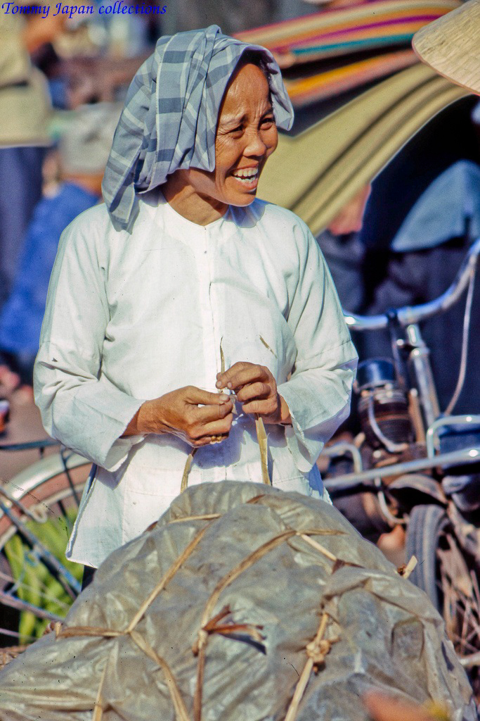 Một cô thím ở chợ Mỹ Tho cười đùa cùng người đi chợ năm 1969   Photo by Lance Crormwell