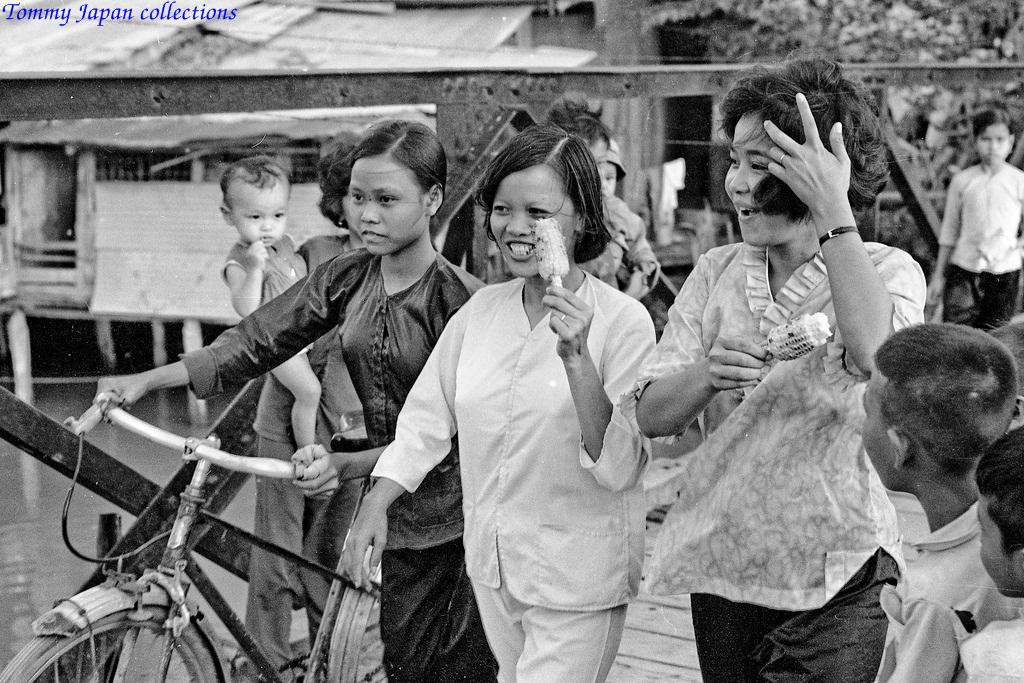 Những cô gái vui cười ăn bắp đi qua một cây cầu