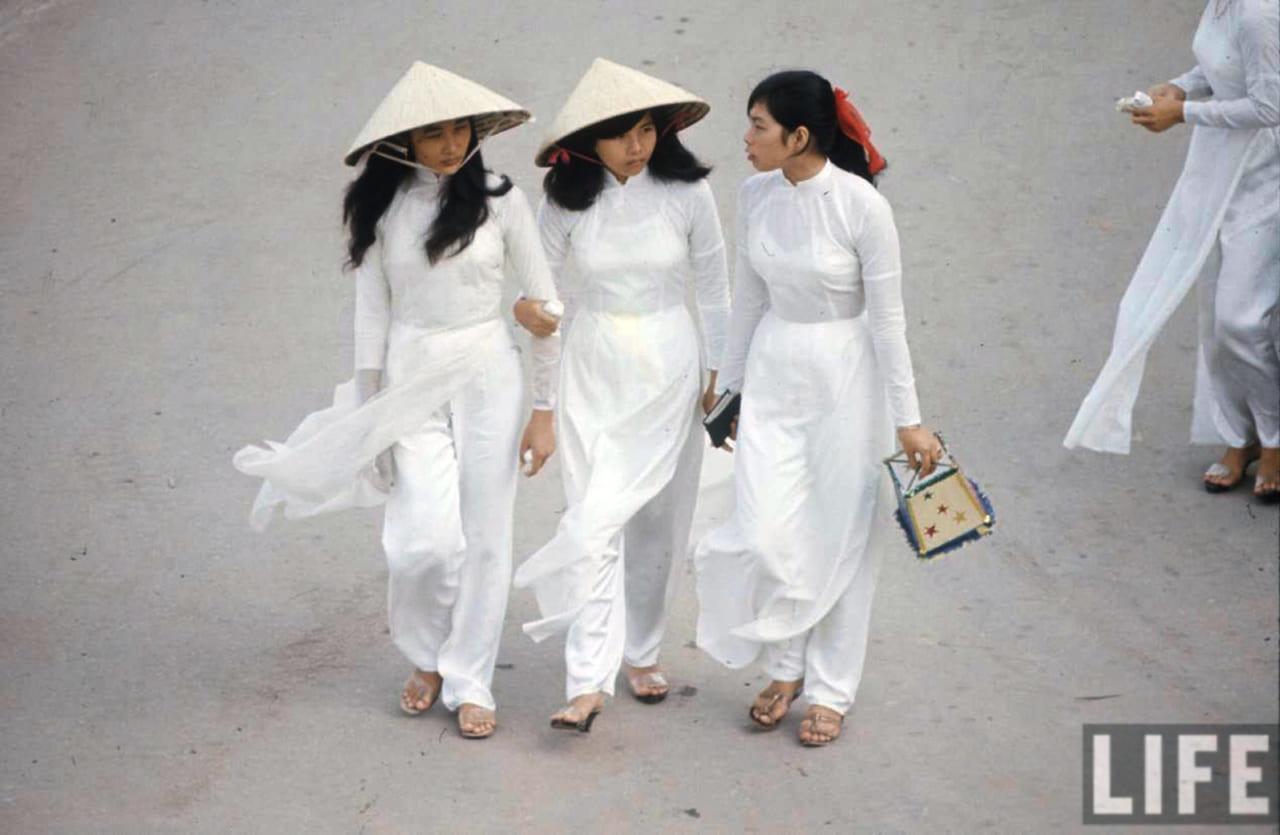 Nữ sinh áo dài cầm vật dụng chứa thông tin phiếu bầu