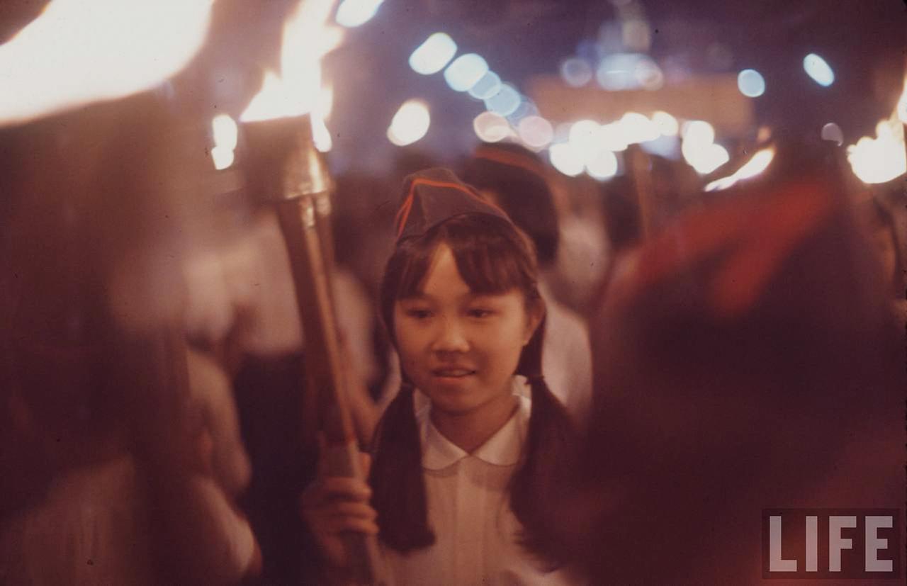 Hình ảnh 1 cô bé học sinh tham gia vào dòng người hủng hộ bầu cử quốc hội năm 1966