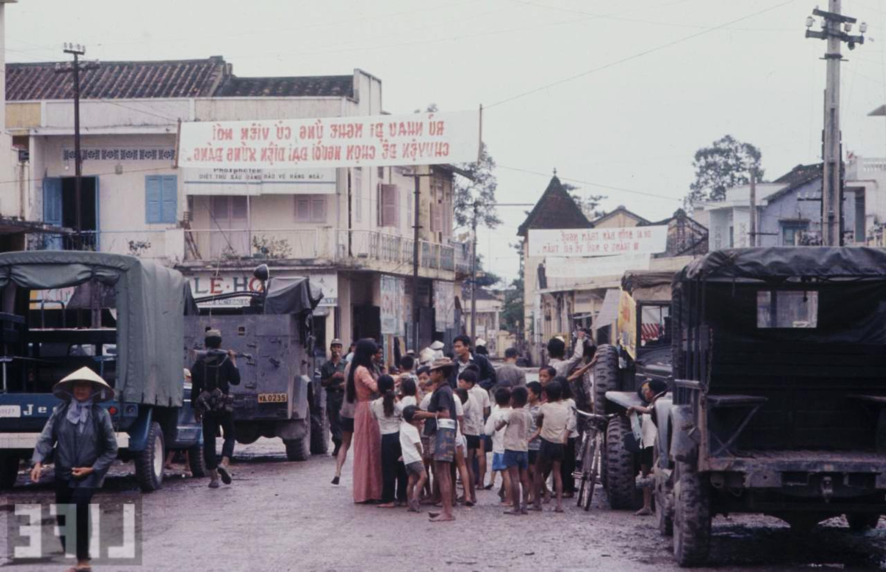Những đứa trẻ quây quanh cô gái phát phiếu thông tin bầu cử quốc hội năm 1966
