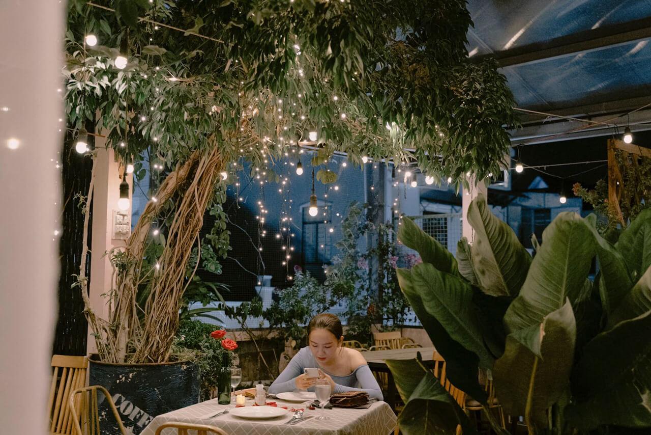 Không gian ăn dưới gốc cây với đèn neon lung linh
