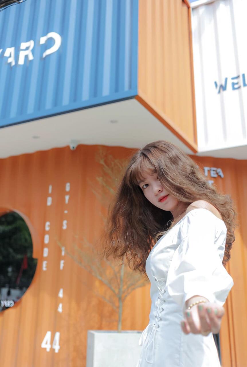 Một bạn nữ chụp ảnh ở khu vực trước cửa quán